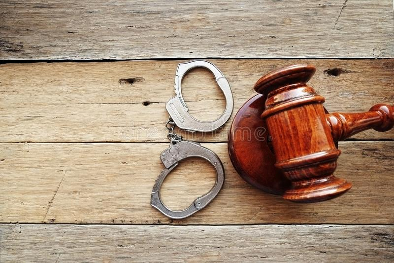 Menottes et marteau de juge sur le fond en bois suggérant commençant un verdict de procès de crime photos libres de droits