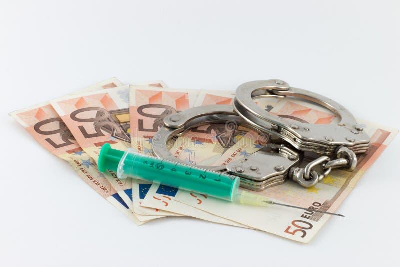 Menottes et seringue sur des factures d'argent photo stock