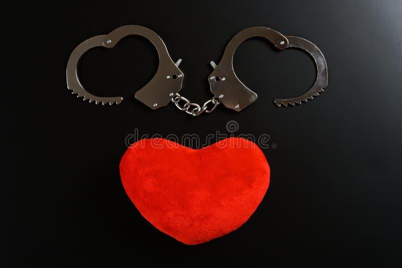 Menottes formées comme des coeurs avec le coeur rouge voisin sur le fond noir images libres de droits