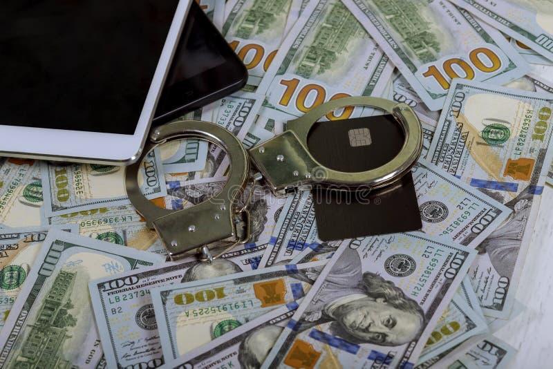 Menottes sur une pile de carte de crédit de billets de banque de dollar US et d'ordinateur portable d'utilisation image stock