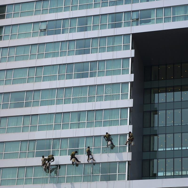 Mens aan het werk aangaande een gebouw royalty-vrije stock afbeeldingen