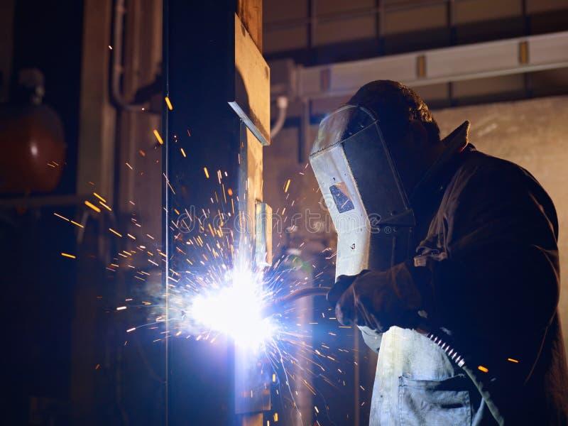 Mens aan het werk als lasser in zware industrie stock afbeeldingen