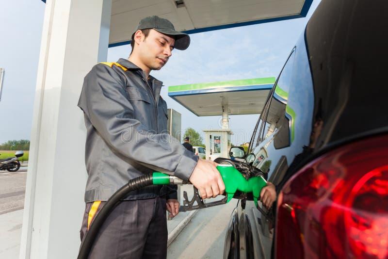 Mens aan het werk bij een benzinestation royalty-vrije stock afbeelding