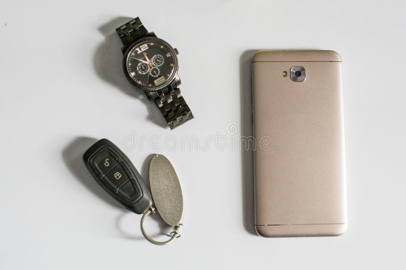 Mens accessories like mobile, car-keys, watch kept on white table or white background royalty free stock photography