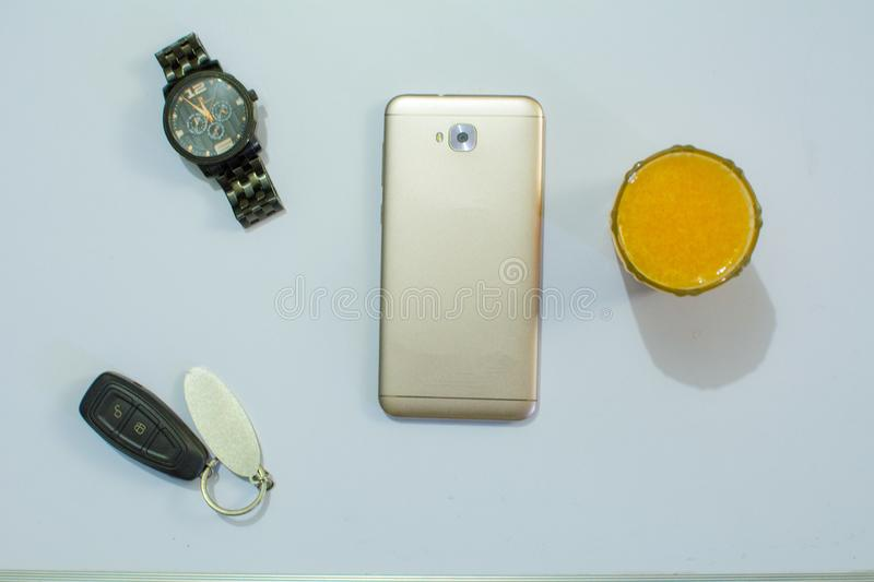 Mens accessories like mobile, car-keys, watch kept on white table or white background stock photo