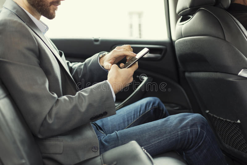 Mens in achtergedeelte van de auto Het typen tekstbericht op mobiele telefoon stock foto's