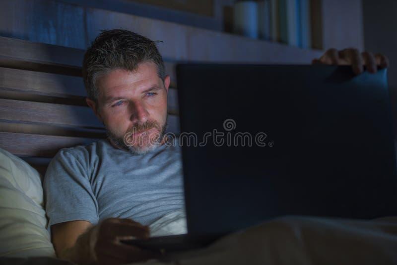 Mens alleen in bed die cybersex gebruikend laptop computer het letten op de film van het pornografiegeslacht laat bij nacht met w stock foto