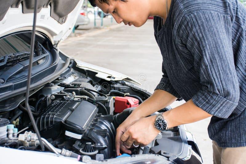 Mens of auto mechanische arbeider die de het motor van een autoolie en onderhoud controleren alvorens te reizen veiligheid stock fotografie