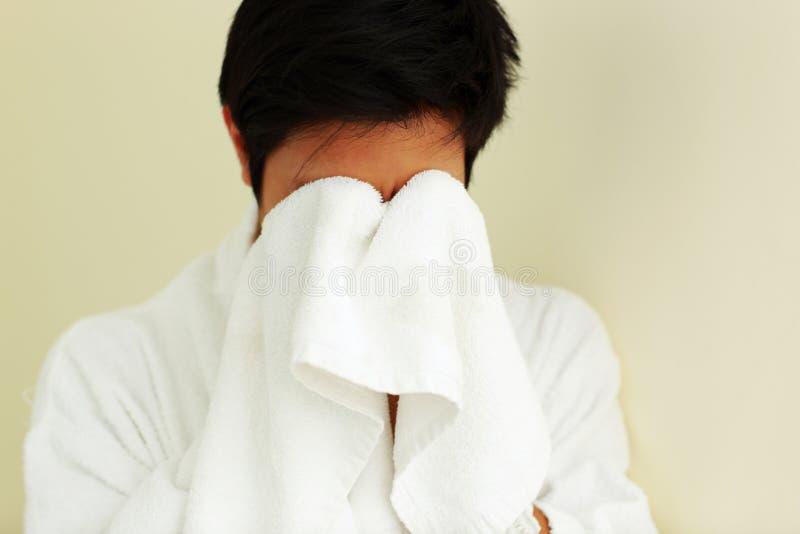 Mens in badjas afvegend gezicht stock afbeelding