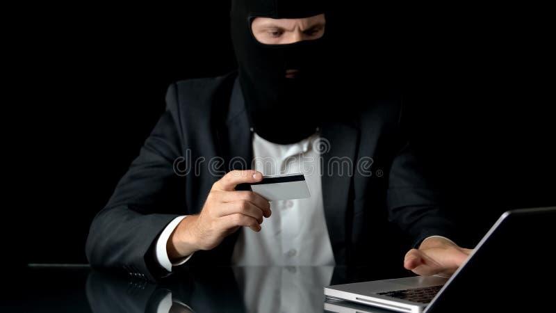 Mens in balaclava en kostuum die bankfraude begaan, die gestolen creditcard, misdaad gebruiken stock afbeeldingen