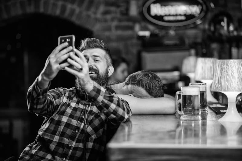Mens in bar het drinken bier Neem selfie foto om grote avond in bar te herinneren De greepsmartphone van mensen gebaarde hipster stock afbeeldingen