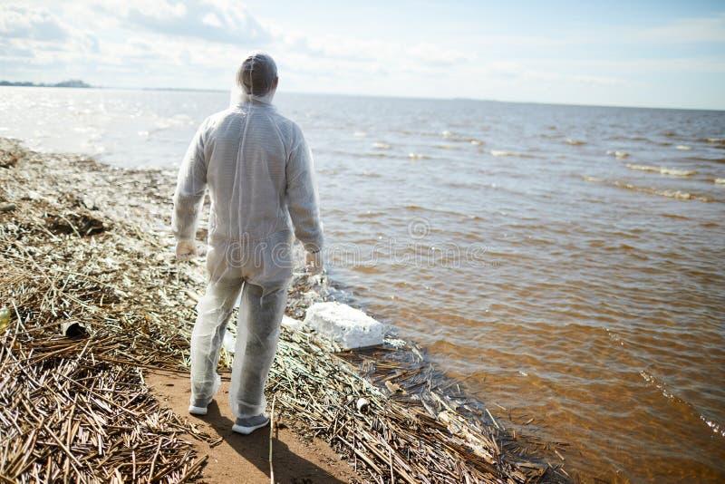 Mens in beschermend kostuum op kust royalty-vrije stock fotografie