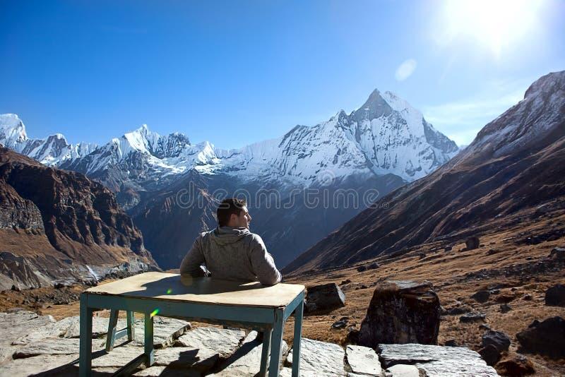 Mens bij bergen stock afbeelding