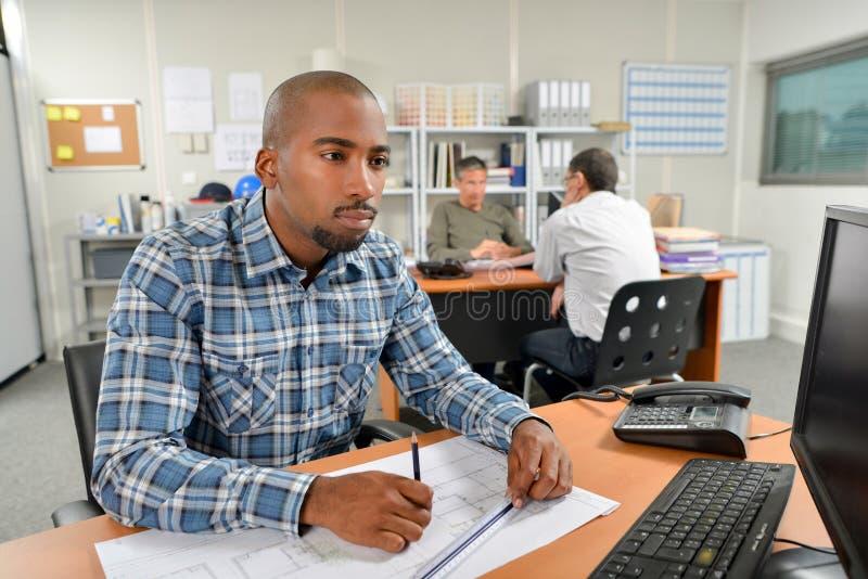 Mens bij bureau die aan schaaltekeningen werken stock afbeeldingen