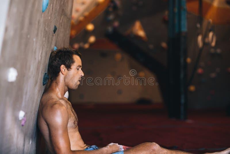 Mens bij een muur die gymnastiek beklimmen die rust nemen stock afbeeldingen