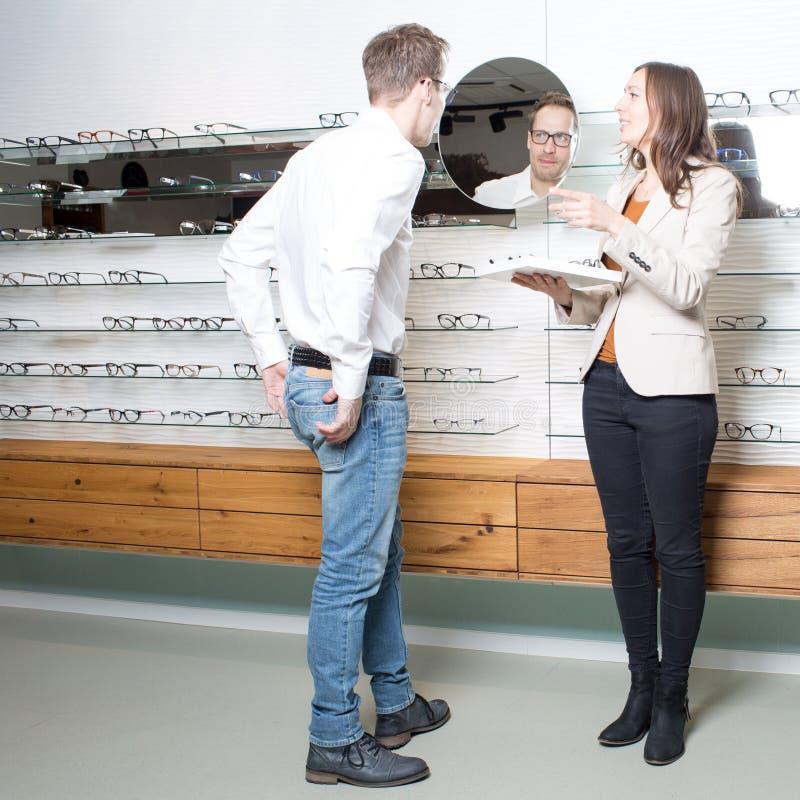 Mens bij een opticien die zijn nieuwe glazen kiezen stock foto