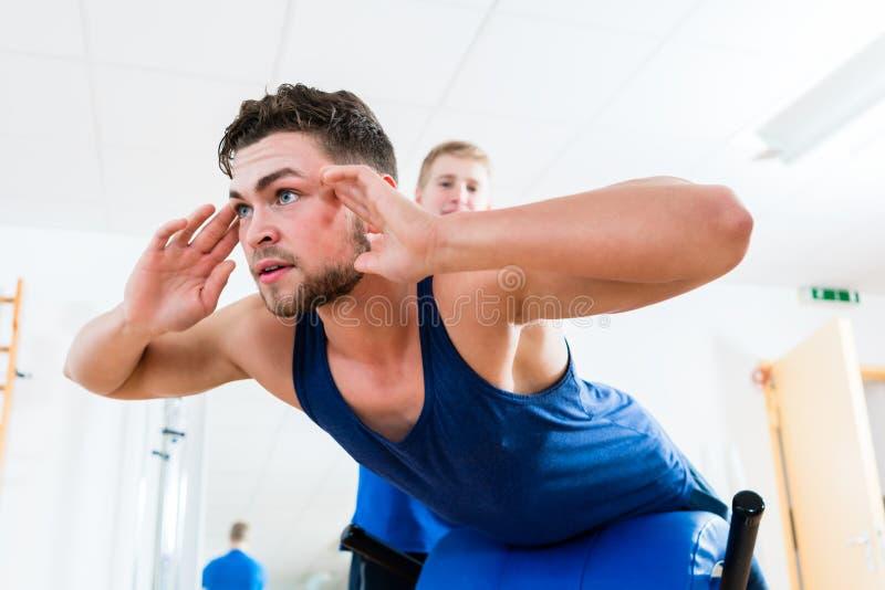 Mens bij gymnastiek op trainingbank die hulp krijgen door persoonlijke trainer stock afbeelding