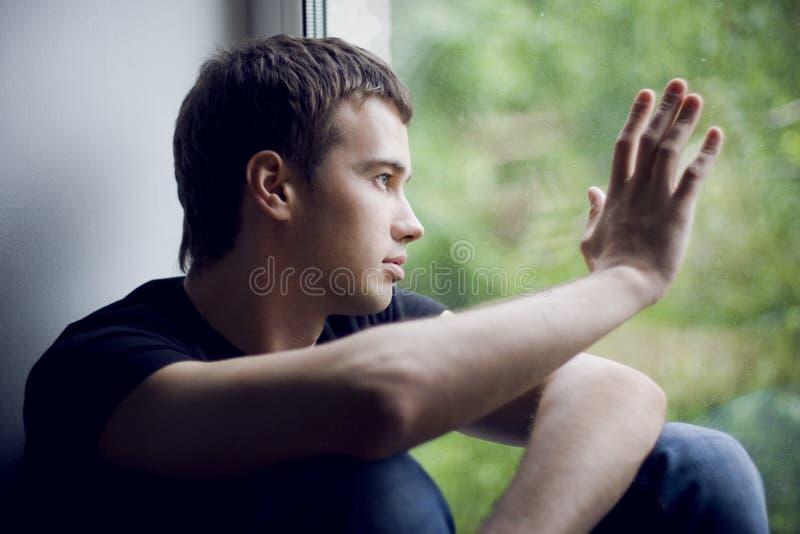 Mens bij het venster stock fotografie