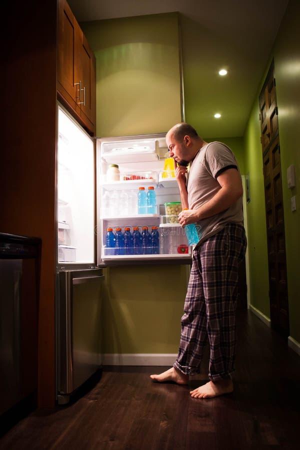Mens bij koelkast