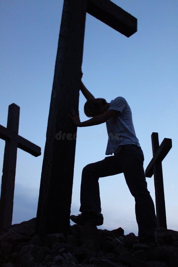 Mens bij kruis 2 stock foto's