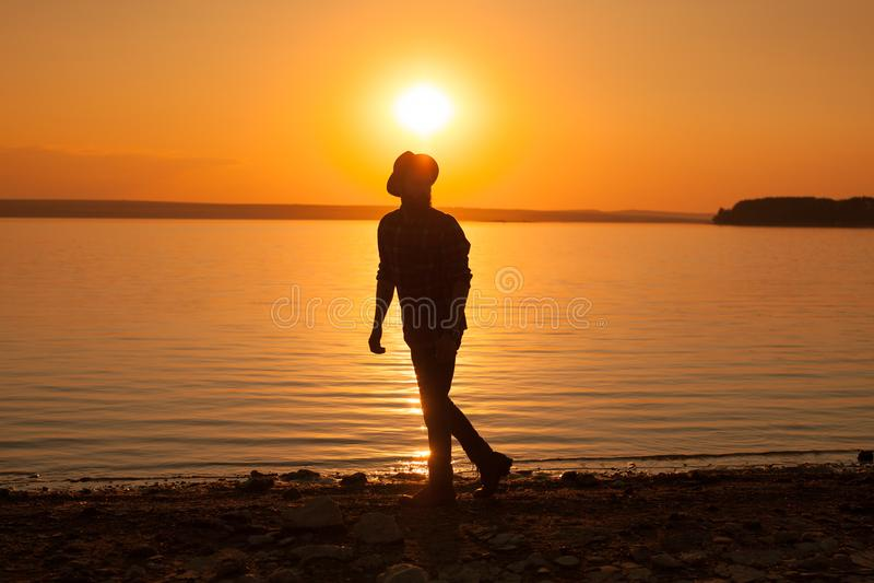 Mens bij meer in zonsondergang stock foto