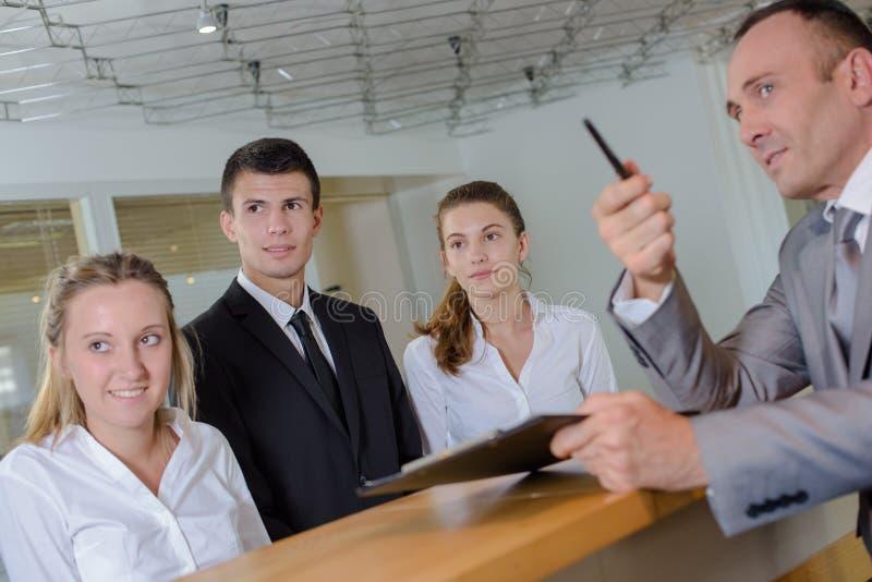 Mens bij ontvangstbureau met jong personeel die links richten stock afbeelding