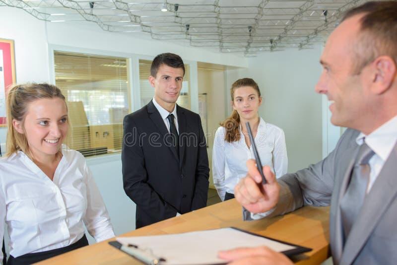 Mens bij ontvangsthotel met arbeiders royalty-vrije stock afbeelding