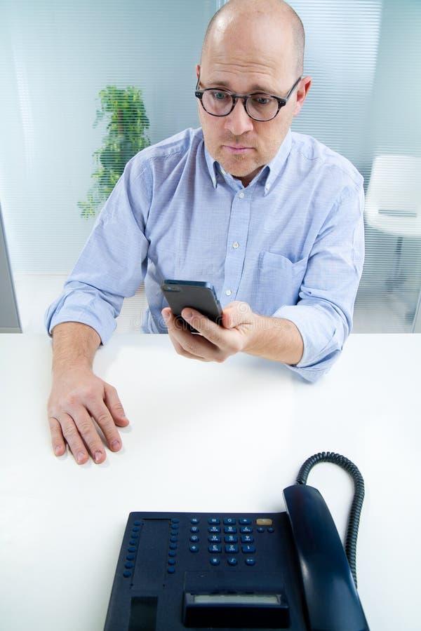 Mens bij zijn mobiele telefoon wordt verrast die stock fotografie