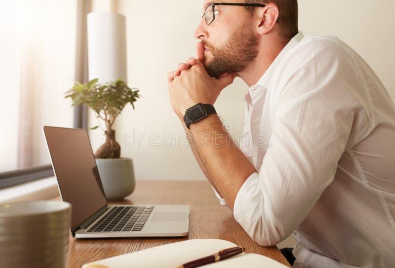 Mens bij zijn workdesk het denken aan bedrijfsoplossingen stock foto's