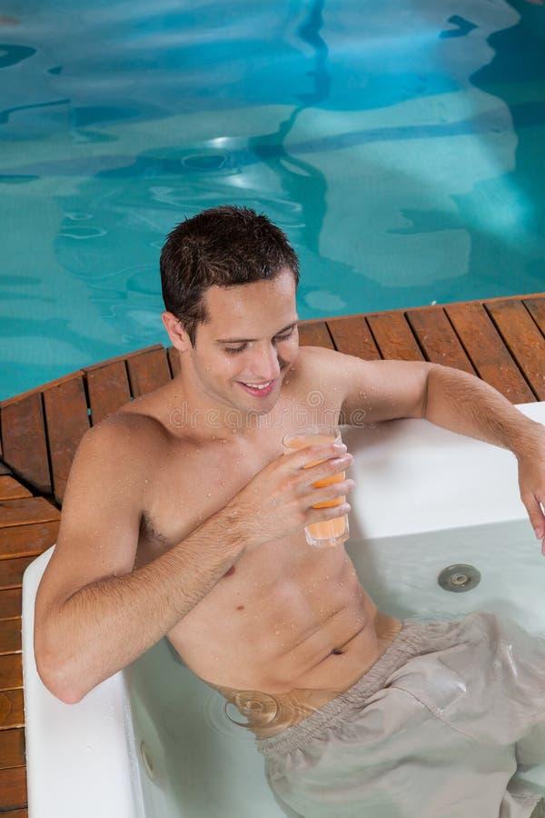 Mens binnen een Jacuzzi het drinken sap stock afbeelding