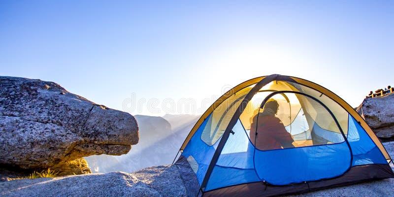 Mens binnen een tent in Yosemite met Halve Koepelmening royalty-vrije stock foto