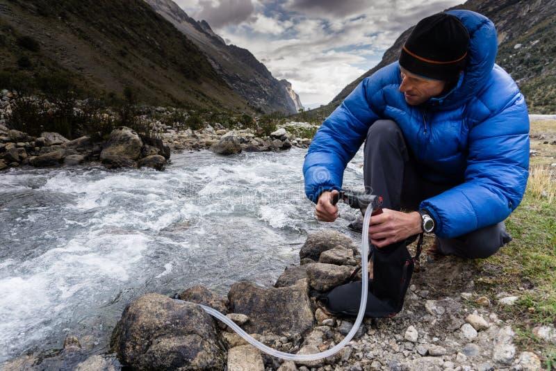 Mens in blauw benedenjasje filtrerend drinkwater van een bergrivier in Peru stock foto's