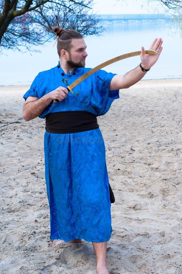 Mens in blauwe kimono met riem, broodje en stokken op hoofdholding zwaard en weg het kijken royalty-vrije stock foto