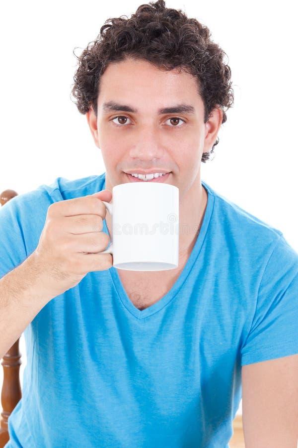 Mens in blauwe t-shirt die en een kop thee koffie zitten drinken royalty-vrije stock afbeeldingen