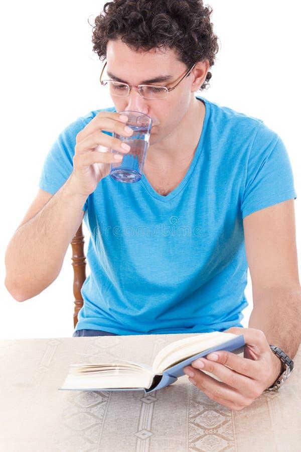 Mens in blauwe t-shirt met glazen die bij lijst zitten en BO lezen stock foto