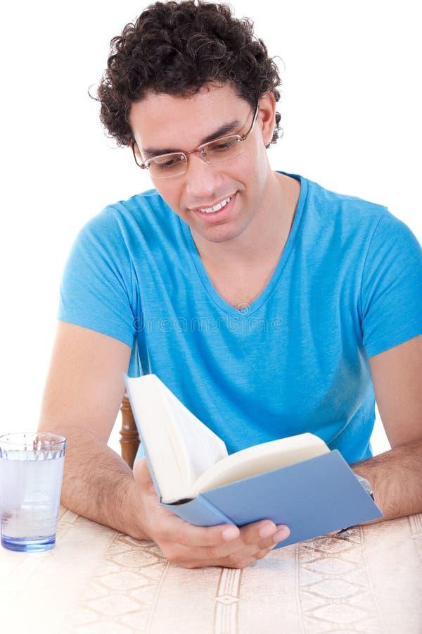 Mens in blauwe t-shirtzitting bij lijst en lezingsboek royalty-vrije stock afbeelding