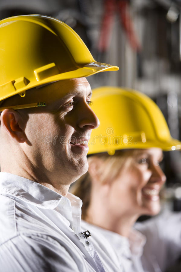 Mens in bouwvakker naast vrouwelijke medewerker stock foto's