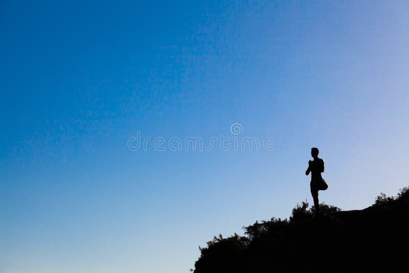 Mens bovenop de berg practing yoga stock afbeelding