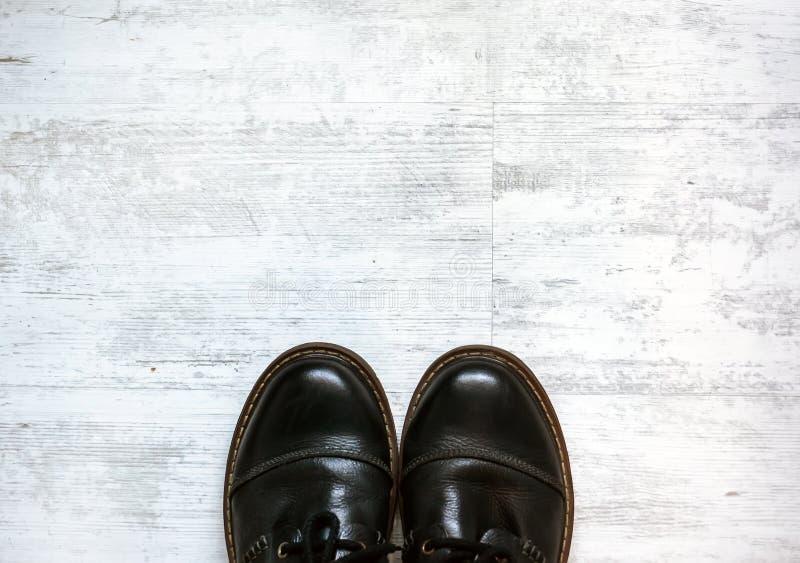 Mens in bruine schoenen die zich op de houten vloerachtergrond bevinden stock foto