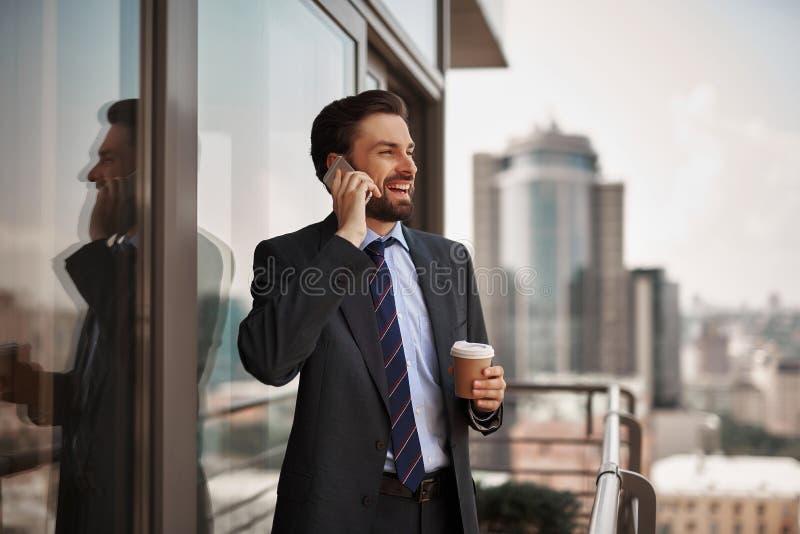 Mens in bureaukostuum die telefonisch op balkon spreken royalty-vrije stock afbeelding