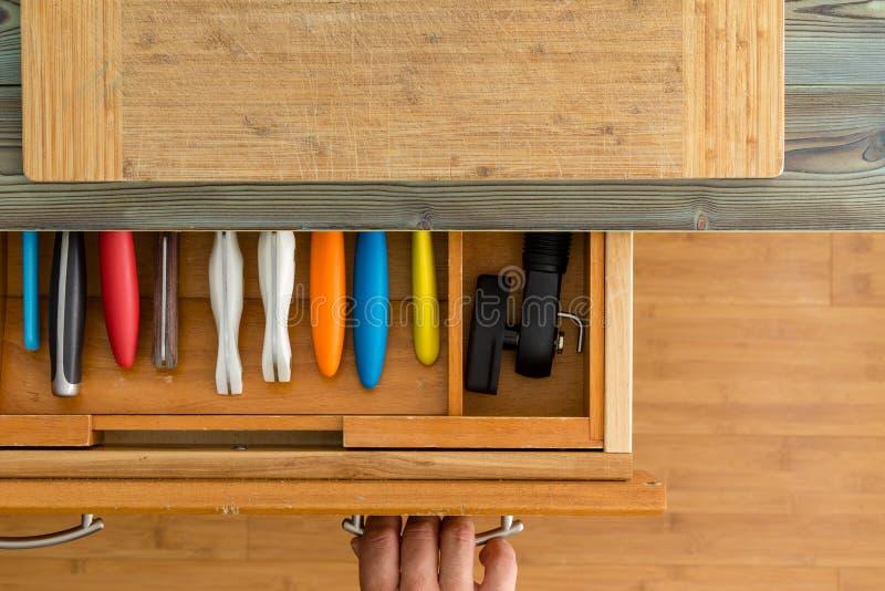 Mens of chef-kok die een messenlade in een keuken openen stock fotografie
