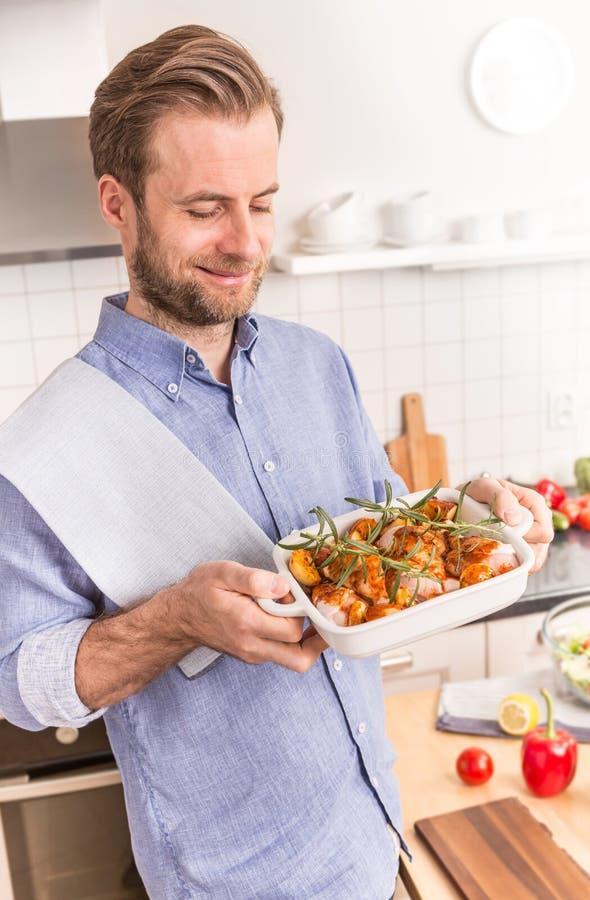 Mens of chef-kokholdings roosterende schotel met ruwe kippentrommelstokken royalty-vrije stock afbeelding