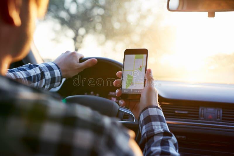 Mens in de auto die mobiele telefoon met kaartgps navigatie houden royalty-vrije stock foto