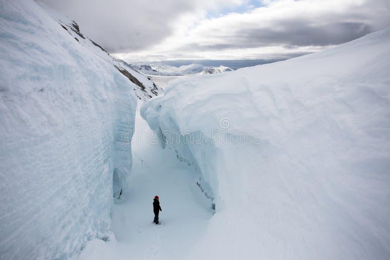 Mens in de diepe gletsjerspleet - het Noordpoolgebied stock fotografie