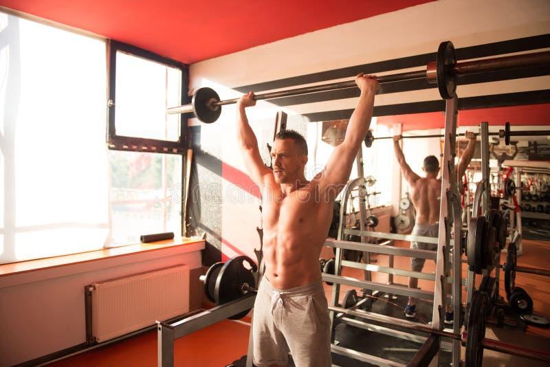 Mens in de Gymnastiek die Schouder met Barbell uitoefenen royalty-vrije stock fotografie