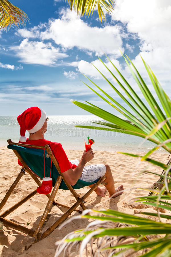 Mens in de hoed van de Kerstman met cocktail op een strand royalty-vrije stock afbeeldingen