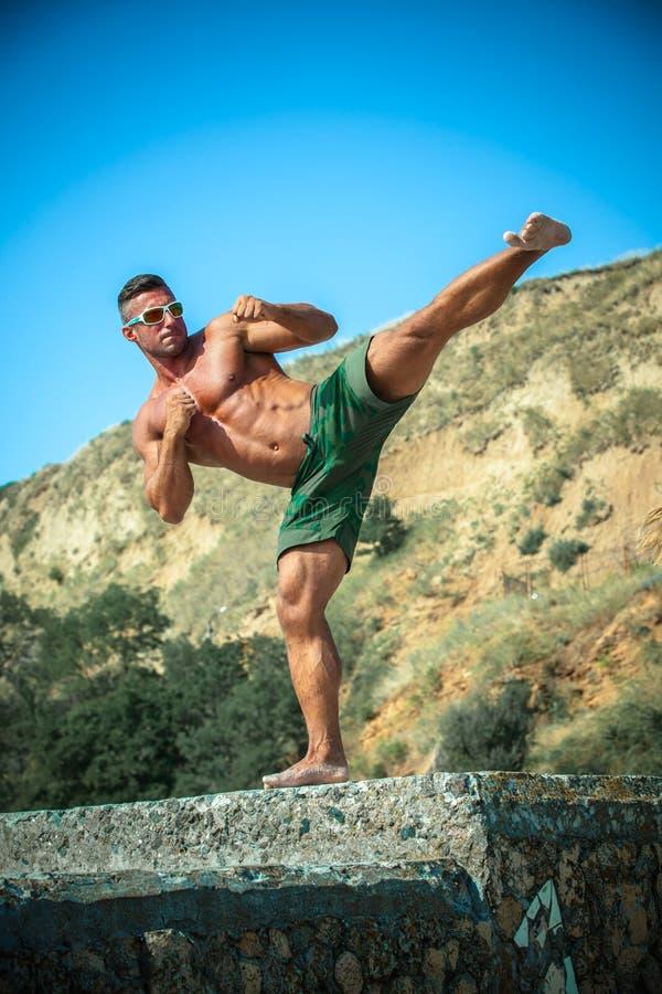 Mens de karate van atletentreinen op een strand stock foto