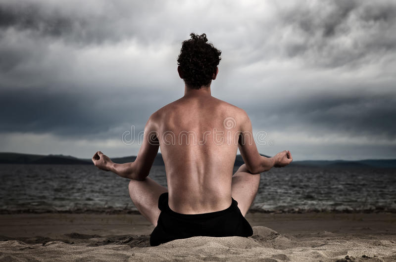 Mens in de meditatie op de kust van het overzees royalty-vrije stock fotografie