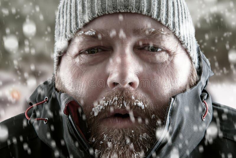 Mens in dichte omhooggaand van het sneeuwonweer stock afbeelding