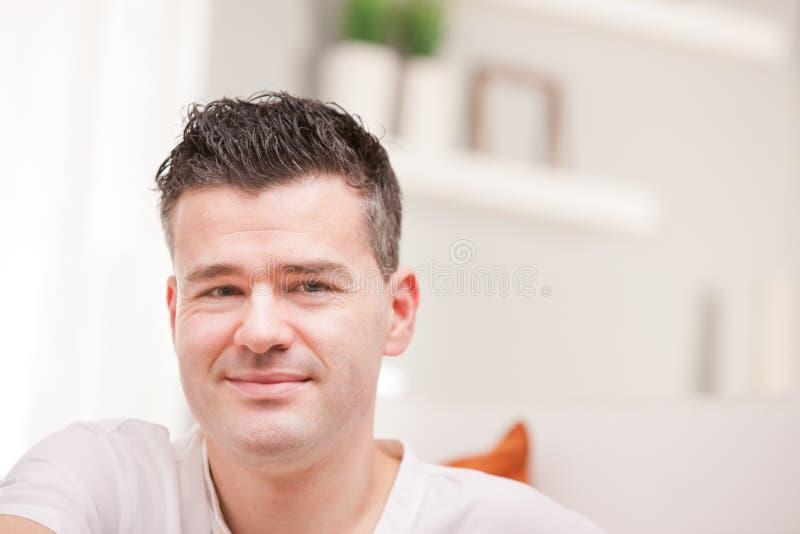 Mens die aan camera het ontspannen in zijn woonkamer glimlachen stock foto's